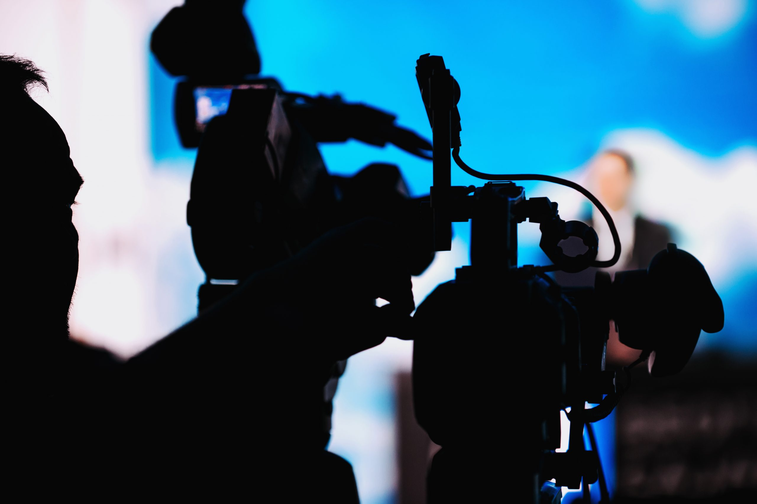 Silhouette of cameraman at media press conference recording presentation of a blurred speake, live streaming concept